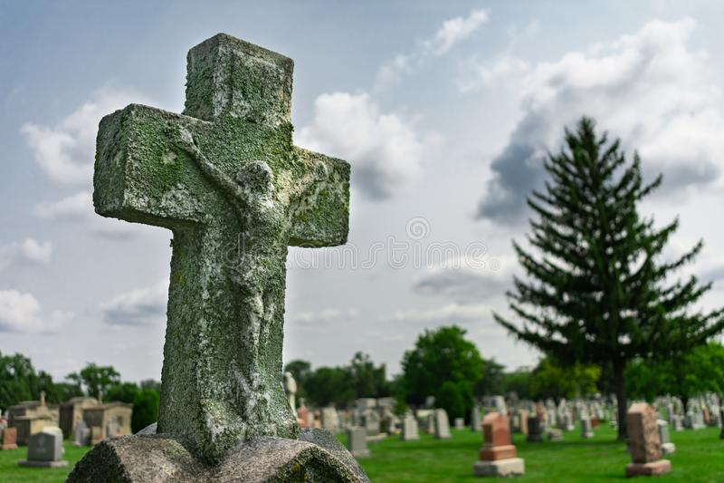 在一块墓碑顶部的老十字架在公墓 库存图片