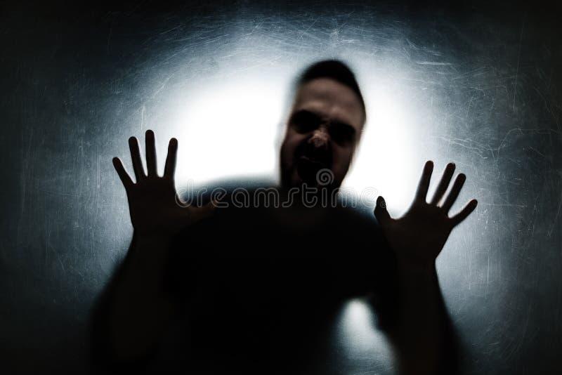 在一块多灰尘的被抓的玻璃后的恼怒的人 图库摄影