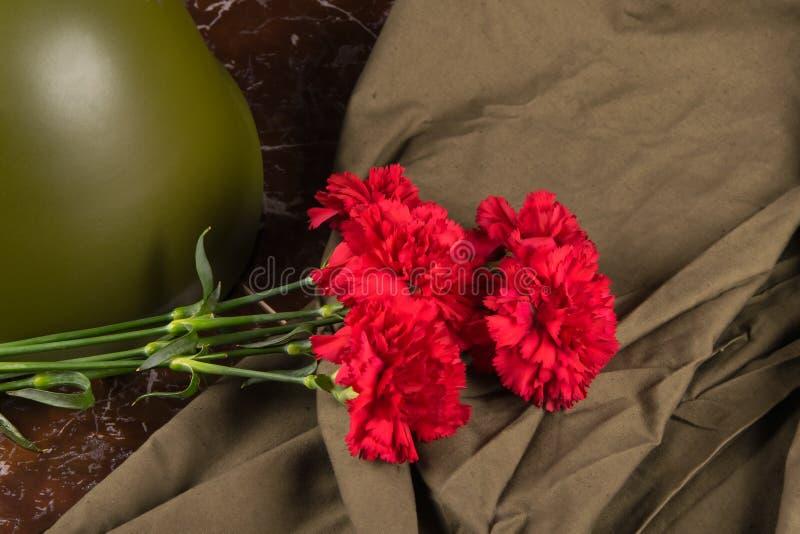 在一块大理石平板、红色康乃馨花束,一件军事盔甲和斗篷帐篷上 库存照片