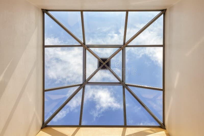 在一块天花板的窗口与蓝天 免版税库存照片