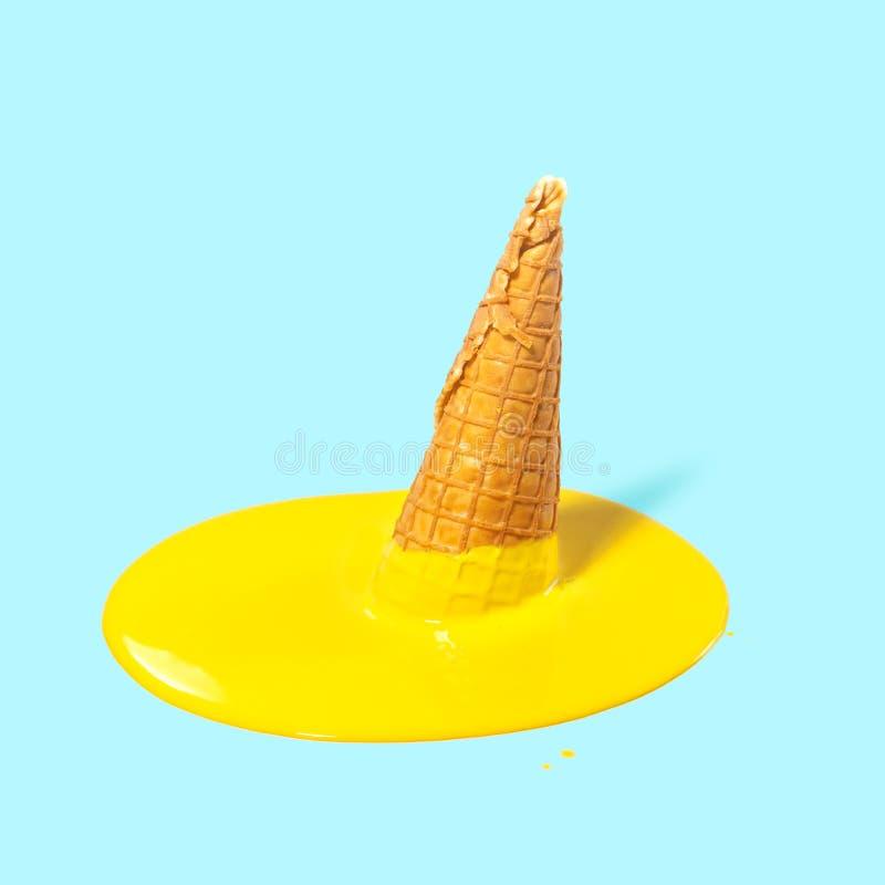 在一块奶蛋烘饼垫铁的熔化黄色果子冰淇淋在浅兰的背景 夏天心情 创造性的概念 免版税库存图片