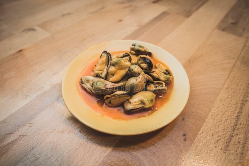 在一块小板材的用卤汁泡的淡菜在一张木桌上 免版税库存图片