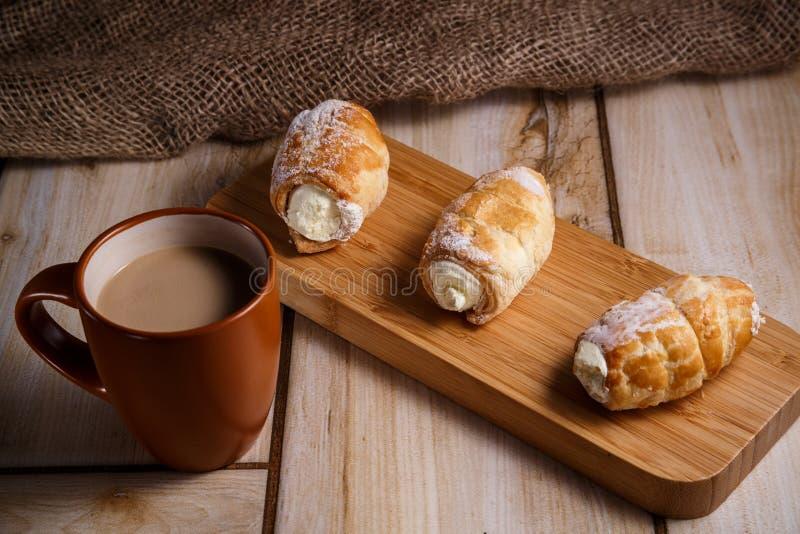 在一块木板材的奶油蛋糕与一杯咖啡与牛奶 自然和好吃的概念 免版税库存照片