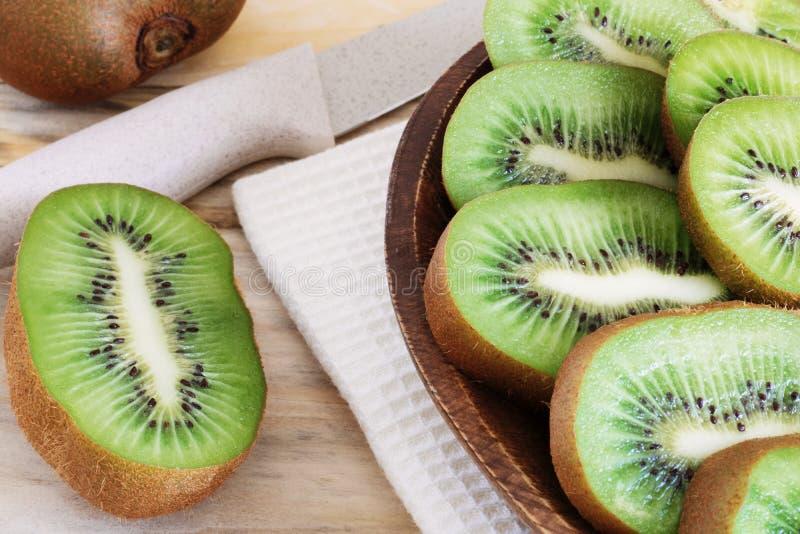 在一块木板材的水多的猕猴桃切片在桌特写镜头,可口果子木头,饮食产品,健康成份,热带f 免版税库存图片