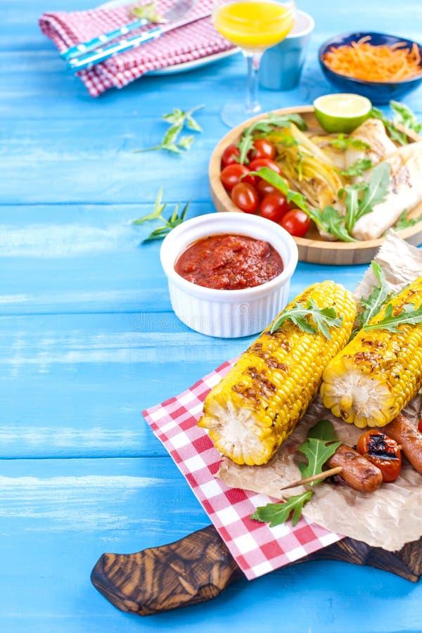 在一块木板材的烤菜和香肠、汁液和沙拉在蓝色背景 面包正餐土豆夏天表蔬菜 文本的空位 复制 图库摄影