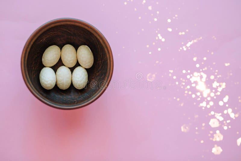 在一块木板材的装饰复活节彩蛋在桃红色背景 库存图片