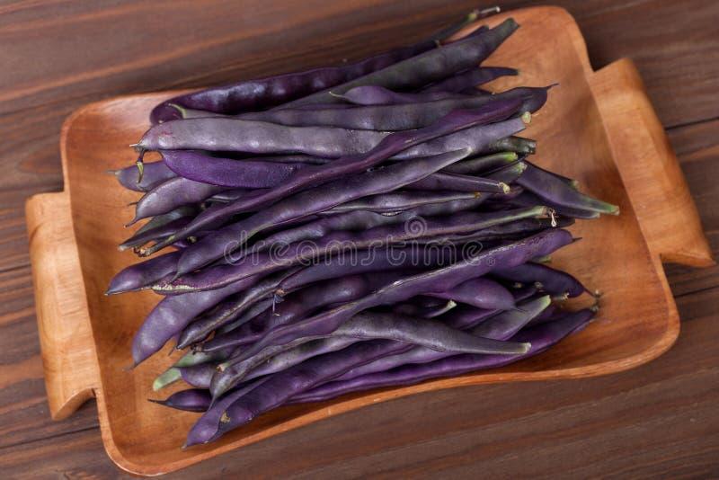 在一块木板材的紫色菜豆在木背景 免版税库存照片