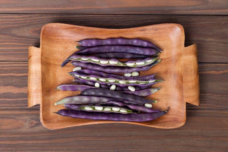 在一块木板材的紫色菜豆在木背景 免版税库存图片