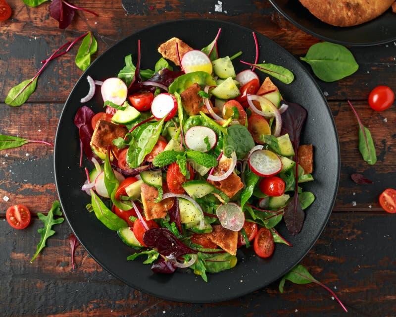 在一块板材用皮塔饼油煎方型小面包片,黄瓜,蕃茄,红洋葱,菜的传统fattoush沙拉混合和草本 库存照片