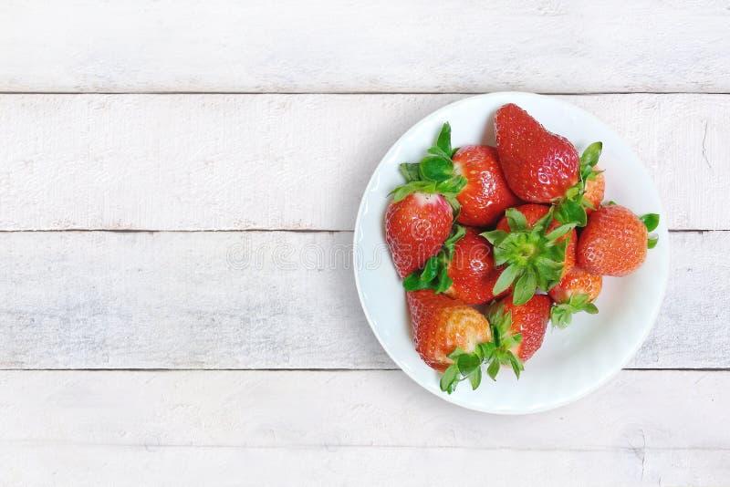 在一块板材的一些新鲜的红色草莓在一个土气厨房的一张白色木桌上 顶视图从上面和空的拷贝空间 免版税库存图片