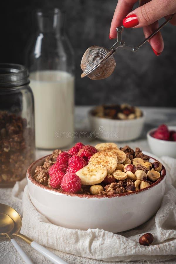 在一块板材的健康早餐格兰诺拉麦片有坚果、香蕉和莓的,牛奶从瓶倒 免版税库存照片