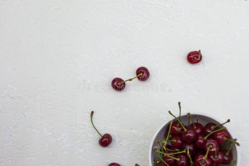 在一块板材的大樱桃在白色背景 免版税库存图片