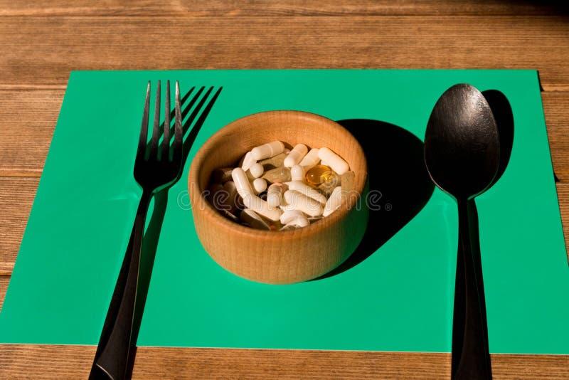 在一块板材的很多五颜六色的药片在一张木桌上 叉子和 免版税库存图片