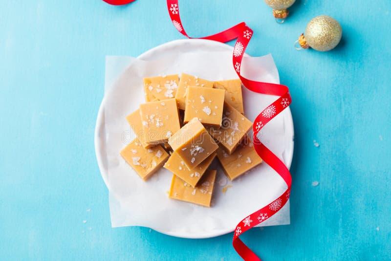 在一块板材的新鲜的焦糖乳脂软糖糖果有在蓝色背景的圣诞节红色丝带的 顶视图 免版税库存照片