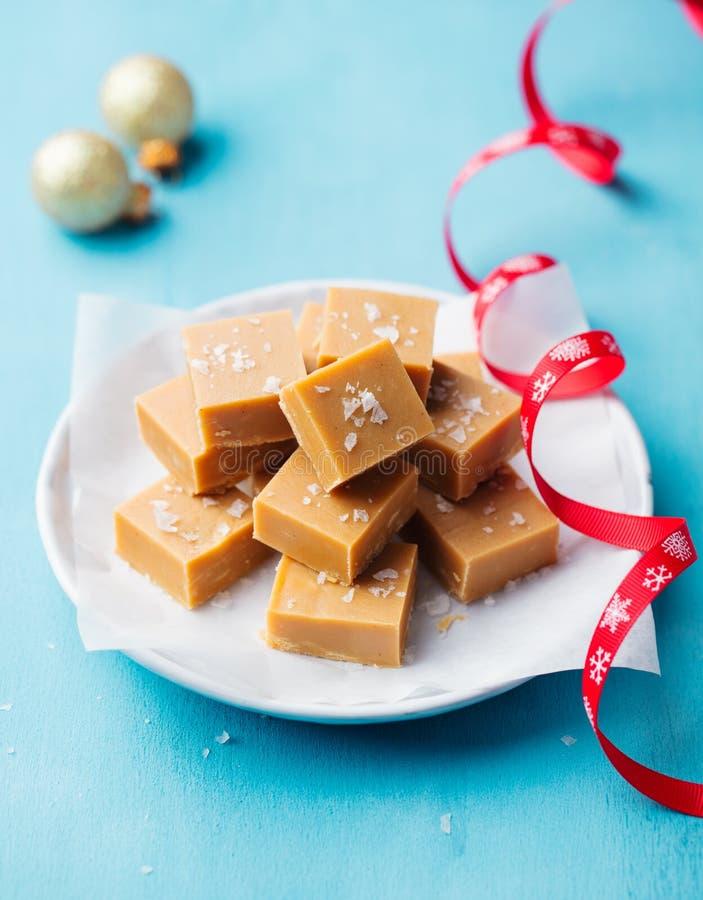 在一块板材的新鲜的焦糖乳脂软糖糖果有在蓝色背景的圣诞节红色丝带的 库存图片