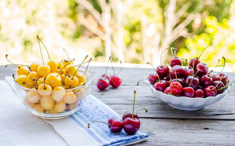 在一块板材的新鲜的红色和黄色樱桃,在gre背景  免版税库存照片