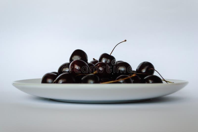 在一块板材的樱桃在白色背景 图库摄影