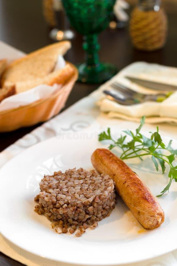 在一块板材的油煎的肉香肠用在黑暗的木桌上的荞麦粥 免版税库存图片