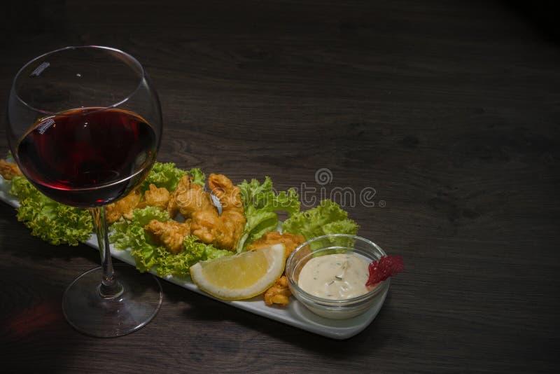在一块板材的油煎的虾用调味汁和一杯在木背景的酒 库存图片