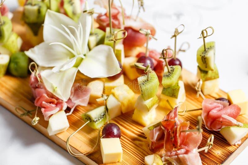 在一块板材的清淡的快餐在自助餐桌上 被分类的微型点心、纤巧和快餐,在事件的餐馆食物 A 免版税库存照片