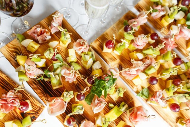 在一块板材的清淡的快餐在自助餐桌上 被分类的微型点心、纤巧和快餐,在事件的餐馆食物 A 免版税库存图片