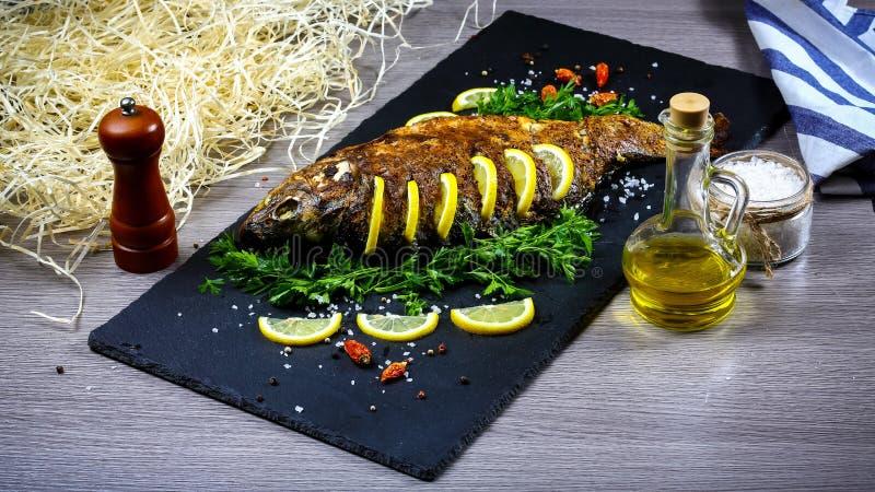 在一块板材的烤河鱼用柠檬和被烘烤的菜和荷兰芹 食物食谱照片,拷贝文本 库存图片