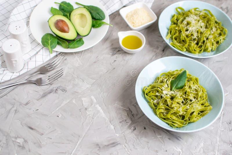 在一块板材的煮熟的绿色菠菜tagliatelle面团用帕尔马干酪和鲕梨调味汁,意大利食物 库存照片
