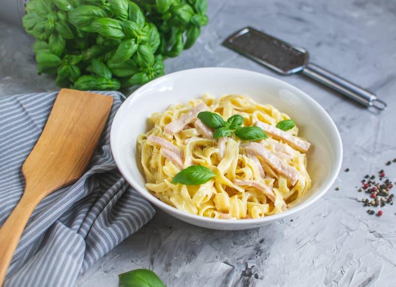 在一块板材的煮熟的tagliatelle面团用Carbonara调味汁、烟肉、蓬蒿和帕尔马干酪 库存图片