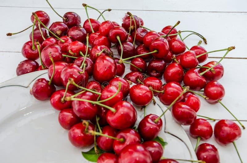 在一块板材的红色甜樱桃在白色背景 r 免版税图库摄影