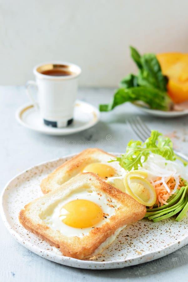 在一块板材的美国早餐有在多士的荷包蛋的,用蕃茄、新daikon、红萝卜、芝麻菜和浓咖啡 煎的鸡蛋 库存图片