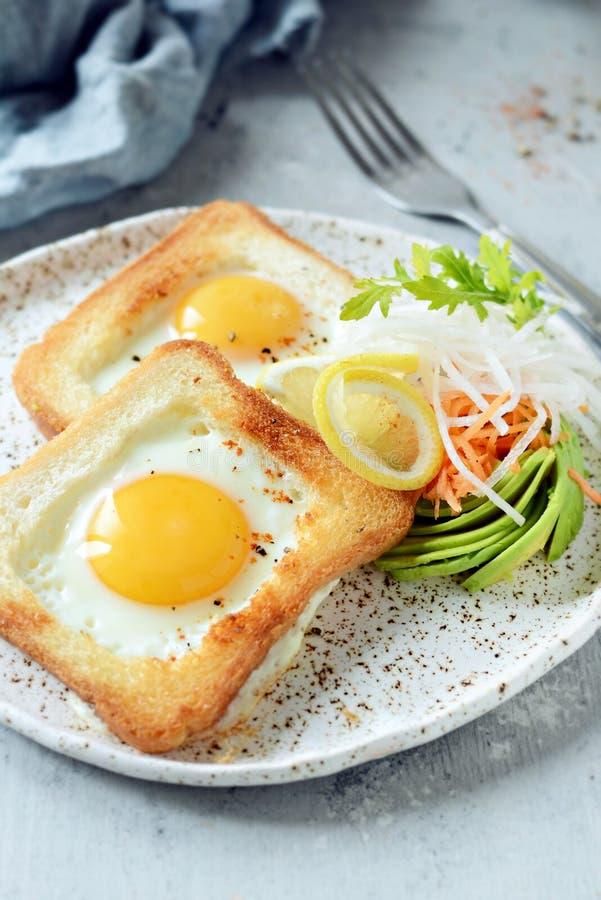 在一块板材的美国早餐有在多士的荷包蛋的,用蕃茄、新daikon、红萝卜、芝麻菜和浓咖啡 煎的鸡蛋 免版税库存照片
