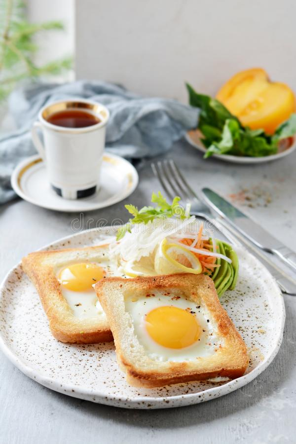 在一块板材的美国早餐有在多士的荷包蛋的,用蕃茄、新daikon、红萝卜、芝麻菜和浓咖啡 煎的鸡蛋 免版税库存图片