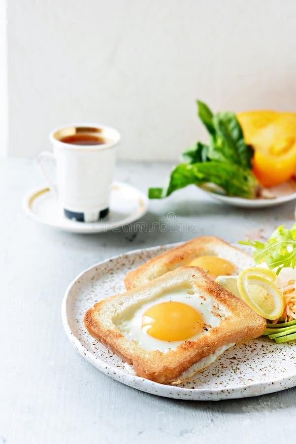 在一块板材的美国早餐有在多士的荷包蛋的,用蕃茄、新daikon、红萝卜、芝麻菜和浓咖啡 煎的鸡蛋 图库摄影