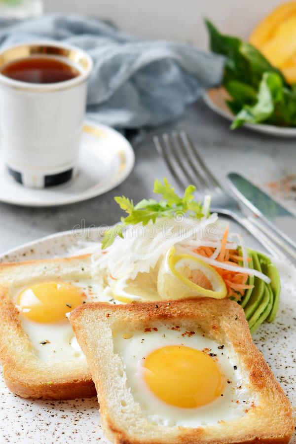 在一块板材的美国早餐有在多士的荷包蛋的,用蕃茄、新daikon、红萝卜、芝麻菜和浓咖啡 煎的鸡蛋 库存照片