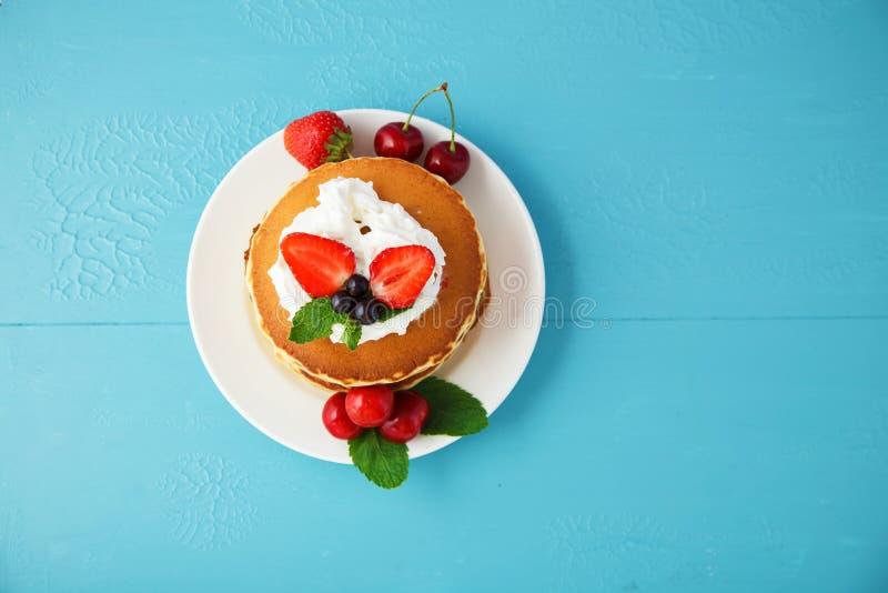 在一块板材的薄煎饼有打好的奶油、草莓、薄菏和甜樱桃的在明亮的蓝色背景 免版税库存图片