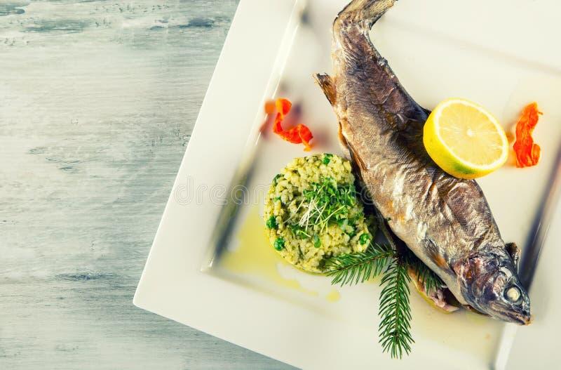 在一块板材的被烘烤的鱼有柠檬和大麦少量的在餐馆 库存图片