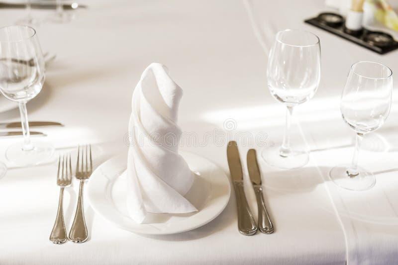 在一块板材的转动的白色餐巾在一张服务的桌上 在咖啡馆的有餐巾和装置的板材或餐馆 库存照片