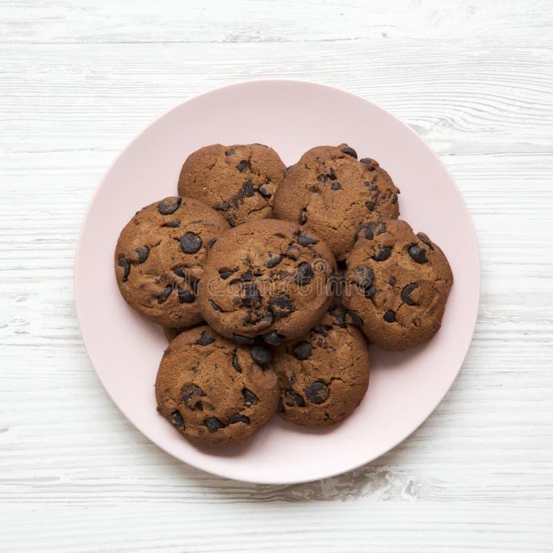 在一块桃红色板材的巧克力曲奇饼在白色木背景 平的位置,顶上 免版税库存照片
