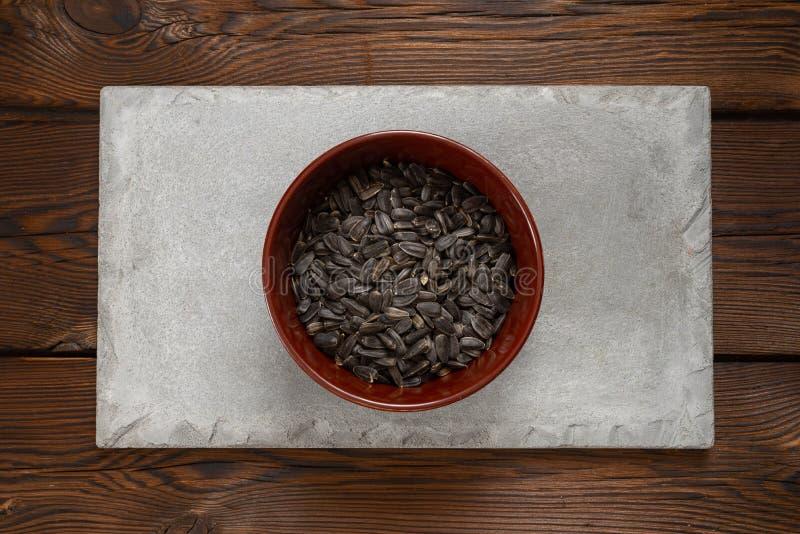 在一块棕色板材的向日葵种子在木背景的一块混凝土瓦 免版税库存照片