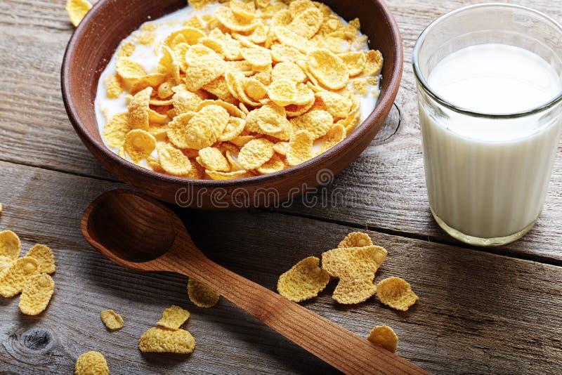 在一块棕色黏土板材的玉米片在破旧的木背景,其次是一杯牛奶和匙子 库存图片