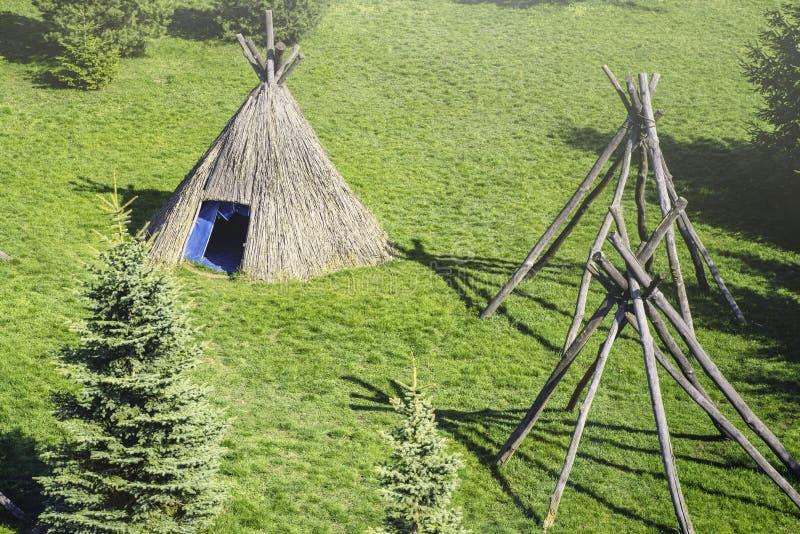 在一块沼地的秸杆圆锥形小屋在一个晴朗的春日 圆锥形小屋类型茅草屋顶小屋 免版税库存图片