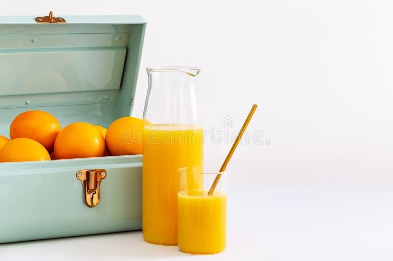在一块玻璃和一个水罐的橙汁过去由充分一只蓝色金属小提箱在白色背景的桔子 库存图片