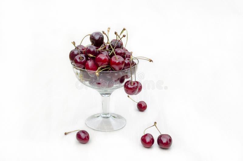 在一块玻璃板的新鲜的成熟甜樱桃 ?? 在碗的樱桃在白色背景 库存照片
