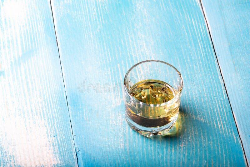 在一块玻璃的伏特加酒在桌上 免版税图库摄影