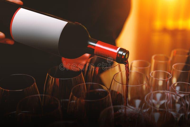 在一块玻璃的侍者倾吐的红酒在事件 免版税库存照片