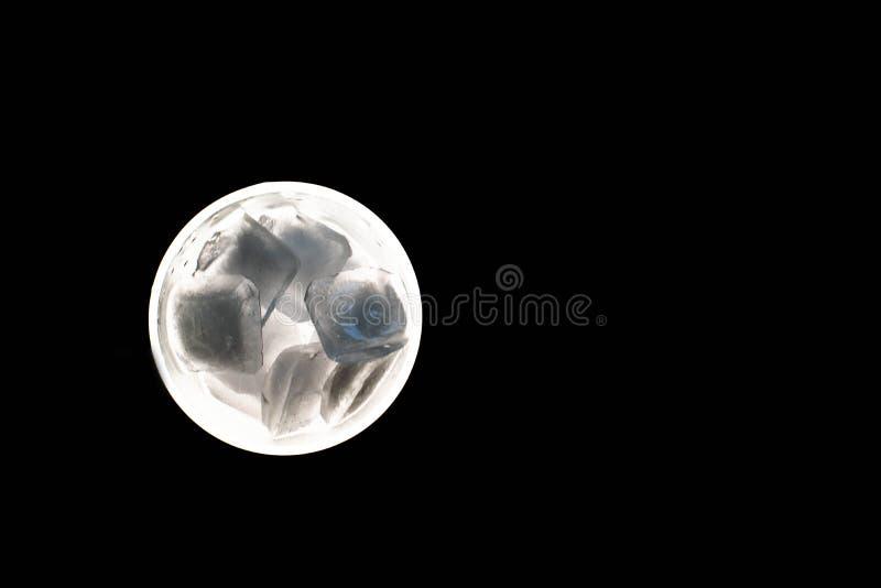 在一块玻璃的冰块在黑背景 免版税库存照片