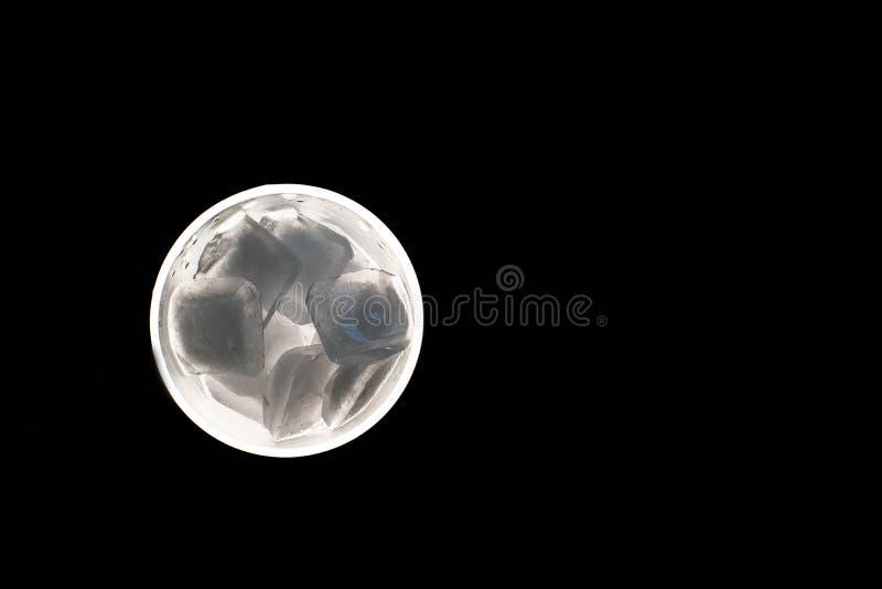 在一块玻璃的冰块在黑背景 免版税图库摄影