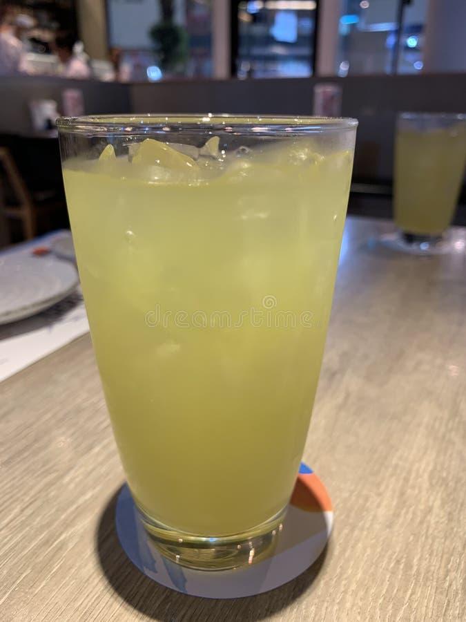 在一块玻璃的冰绿茶在一张木桌上 免版税库存图片