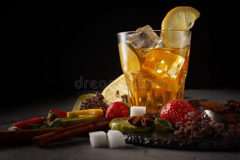 在一块玻璃的冰茶在一个黑色的盘子用饼干、甜点和果子在黑背景 免版税库存图片