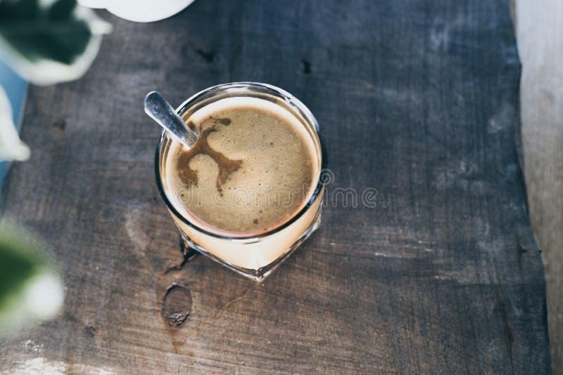 在一块玻璃的咖啡在一张木桌上 免版税库存图片